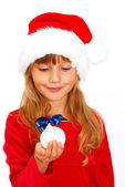 Young girl in santa cloth with christmas ball in hand — Stock Photo