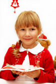 Little girl with christmas eve wafer on plate — Stock Photo