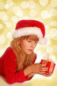 Chica con regalo de Navidad sobre fondo brillante — Foto de Stock
