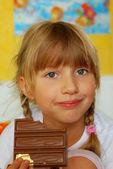 Little girl eating chocolate — Stock Photo