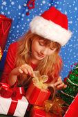 Girl and christmas gifts with snowy background — Stock Photo