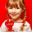 Stock Photo: Little girl with heart shape lolly