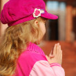 Little girl praying in front of church — Stock Photo