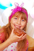 Young girl eating donuts on party — Stock Photo