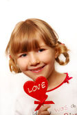 Little girl with heart shape lolly — Stock Photo