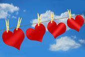 Red hearts on clothesline against blue sky — Stock Photo