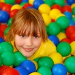 Happy girl in ball pool — Stock Photo