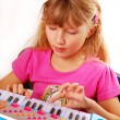 Stock Photo: Little girl playing piano keyboard
