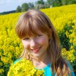 Young girl in rape field — Stock Photo