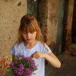 Foto Stock: Young girl with bunch of lilac