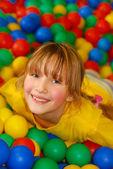 Happy girl in ball pool — Stock Photo