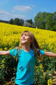 Happy young girl in rape field — Stock Photo