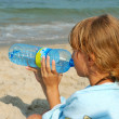 Stock Photo: Young girl drinking water on the beach