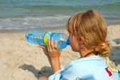 Young girl drinking water on the beach — Stock Photo