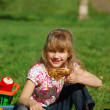 Young girl eating on picnic — Stock Photo