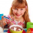 Girl eating chocolate cornflakes — Stock Photo