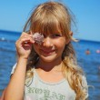 Young girl on beach with shell — Stock Photo