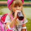 Stock Photo: Young girl drinking and rollerskating