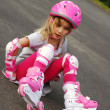 Stock Photo: Young girl rollerskating-falling down