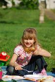 Young girl eating on picnic — Stock Photo