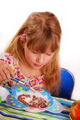 Girl eating chocolate cornflakes — Stock Photo