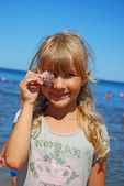 Young girl on beach with shell — ストック写真