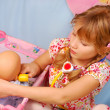 Foto Stock: Little girl playing with baby doll