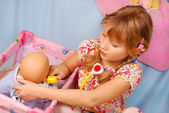 Little girl playing with baby doll — Stok fotoğraf