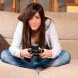 Young female concentrating playing videogames on sofa at home — Stock Photo #3974432