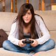 Young female concentrating playing videogames on sofa at home - Стоковая фотография