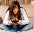 Young female concentrating playing videogames on sofa at home — Stock Photo #3974456