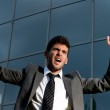 Young successful businessman celebrating a goal on a modern building backgr — Stock Photo #3974573