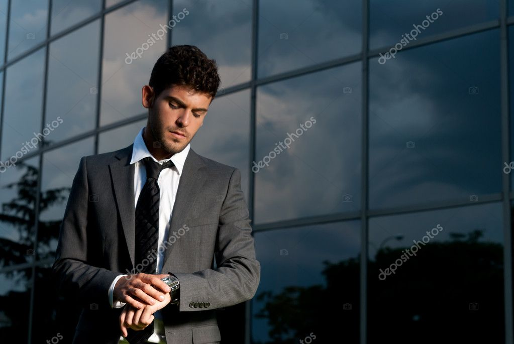 Young businessman looking clock at night on modern building background  Stock Photo #3974620