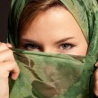 Young arab womwith veil showing her eyes on dark gray background — Stock Photo #4217572