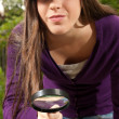 Young woman with magnifier glass and hat looking for something on outdoors — Stockfoto