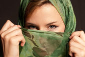 Young arab woman with veil showing her eyes on dark gray background — Stock Photo