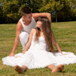 Young couple happy sitting on grass white clothes, love relationship — Стоковая фотография