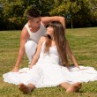 Young couple happy sitting on grass white clothes, love relationship — Photo