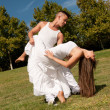 Young beautiful couple dance and embrace on grass over sky — Stok fotoğraf