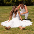 Young couple happy sitting on grass white clothes, love relationship — Stok fotoğraf