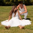 Young couple happy sitting on grass white clothes, love relationship — Stock Photo