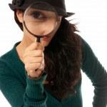 Молодая женщина, глядя через увеличительное стекло лупа детектив изолированные на wh — Стоковое фото