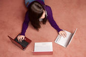 Young woman multitasking with three laptop lying on floor — Stock Photo