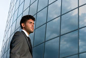 Young businessman looking to good future on modern building background — Stock Photo