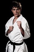 Karate male fighter young high contrast on black background. — Stock Photo