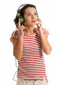 Young woman listening music with headphones standing on white background — Stock Photo
