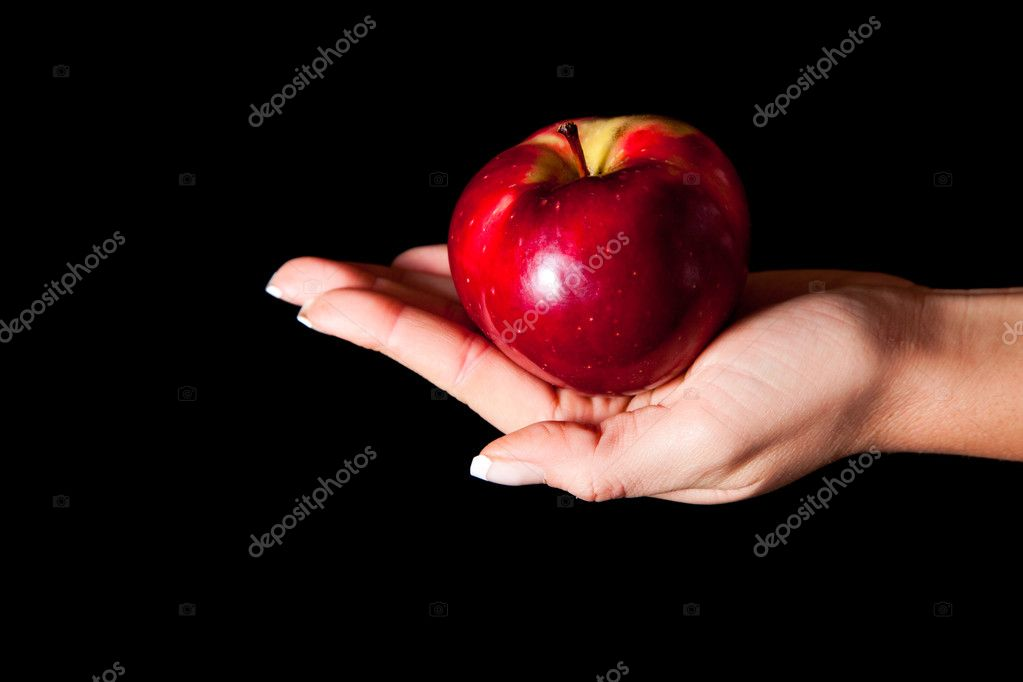 Woman hand giving an apple to man on black background - Stock Image