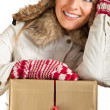 Caucasian blond woman in furry hat and christmas gifts isolated on white - Stock Photo
