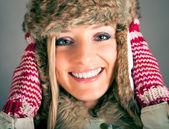 Portrét krásné blonďaté ženy v teplé oblečení na modrém pozadí — Stock fotografie