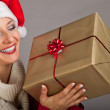 Woman in santa hat with christmas presents — Stock Photo #4415991